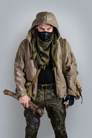 Young handsome man with ax wearing black protective face mask and jacket with hood on gray