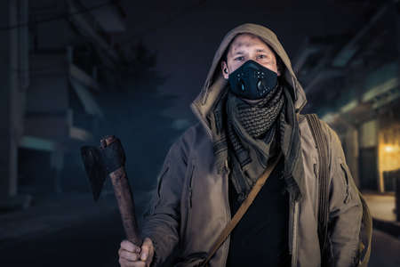 Young handsome man with ax wearing medical protective face mask and hood in the street