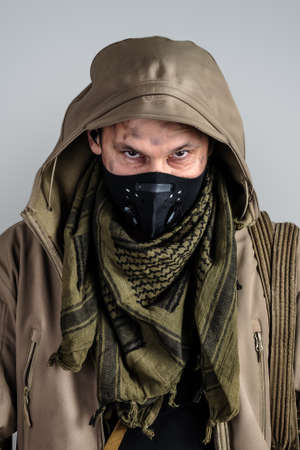 Young handsome man wearing black protective face mask and jacket with hood on gray