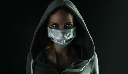 Dark photo of Young serious riot woman wearing medical protactive face mask and hood in the night on black background