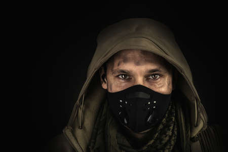 Dark photo of Young handsome man wearing black protactive face mask and hood on black background