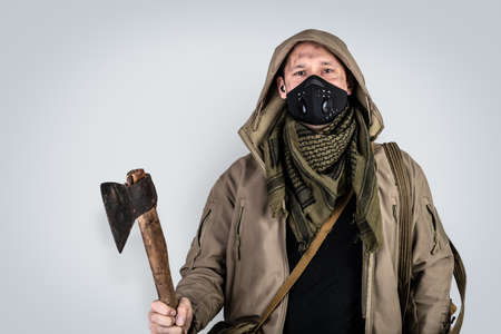 Dark photo of Young handsome man with ax wearing black protactive face mask and jacket with hood isolated on gray background