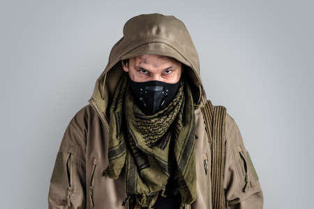 Dark photo of Young handsome man wearing black protactive face mask and jacket with hood isolated on gray background