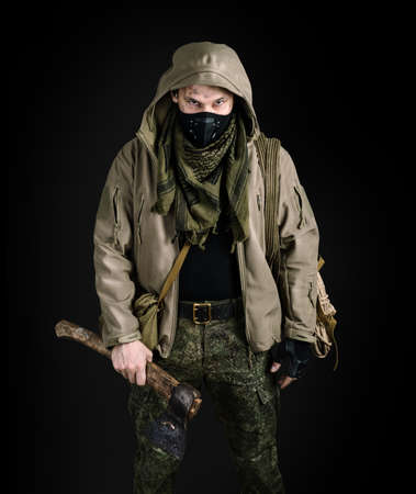 Dark photo of Young handsome man with ax wearing black protactive face mask and jacket with hood isolated on black background