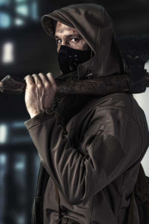 Dark photo of Young handsome man with ax wearing medical protactive face mask and hood in the street of night usa city