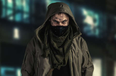 Dark photo of Young handsome man wearing black protactive face mask and hood in the street of night usa city