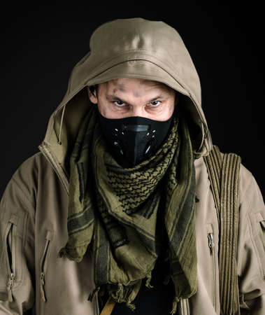 Dark photo of Young handsome man wearing black protactive face mask and jacket with hood on black background isolated