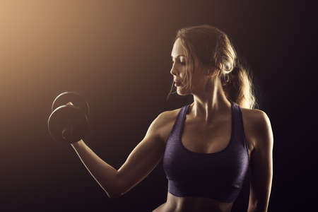 Slim athletic woman on black background in gym. Holding dumbbell in the hand
