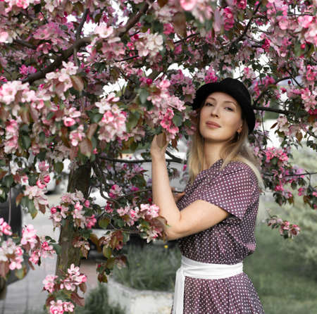 Portrait of a beautiful woman wearing black brimmed hat among spring foliage and pink flowers of apple wearing polka-dot fashion summer dress