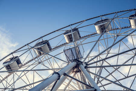 Gray or white metal ferris wheel with closed passenger cabins close-up in the amusement park Standard-Bild