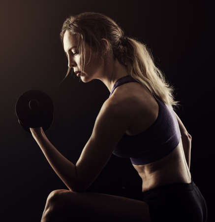 Slim athletic woman Holding dumbbell in the hand on black 写真素材