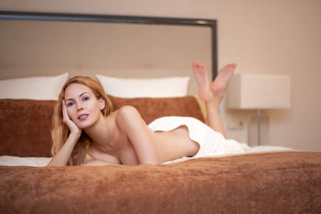 Young blond lovely woman lying on bed in light bedroom at home or spa hotel