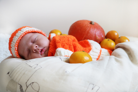 Cute peaceful sleeping newborn baby dressed in a knitted orange costume with oranges around of him on white blanket. Banque d'images