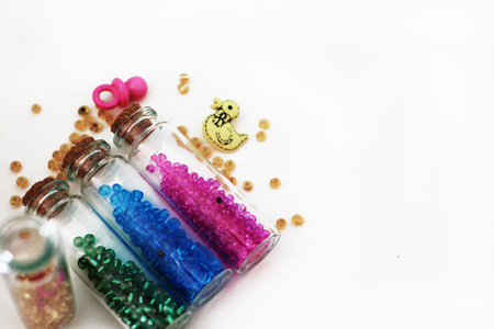 Tiny glass bottles filled with colorful beads and elements for a baby spilling out, isolated on white background with space for text. Stock Photo