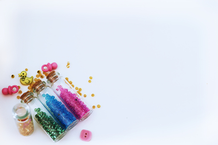 Tiny glass bottles filled with colored beads and elements for baby spilling out, isolated on a white background with space for text. Stock Photo