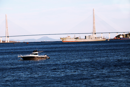 View on Golden brige in Vladivostok city with a ship and little yacht in the bay. Stock Photo