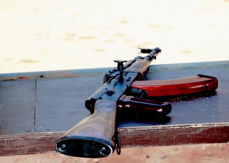 Close up of kalashnikov ak 47 machine gun lying on  shabby wooden table surface on defocused blurred background.