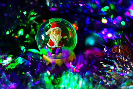 Glass snowball with santa claus inside on festive blurred background with sparkling lights and tinsel. Christmas and new year magical background, template.