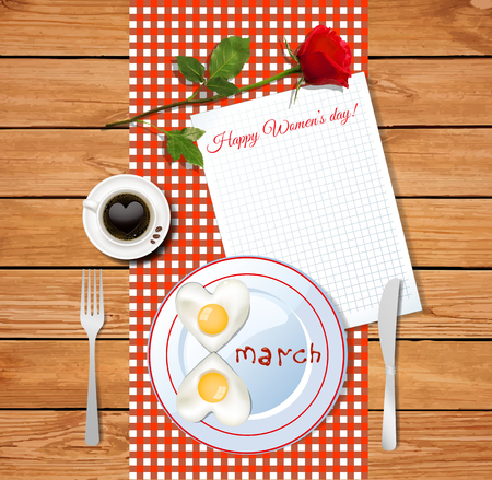 Happy womens day greeting card with two  heart shaped fried eggs, a fork and knife and a cup of coffee on a red and white checked tablecloth