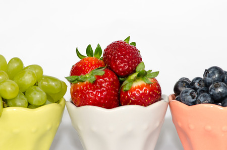 bilberries: strawberry, grape and bilberries in bowl on white background