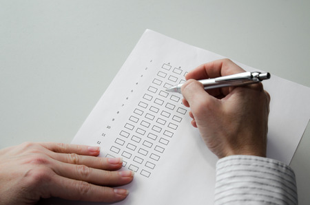 hand with pen filling in a questionnaire photo