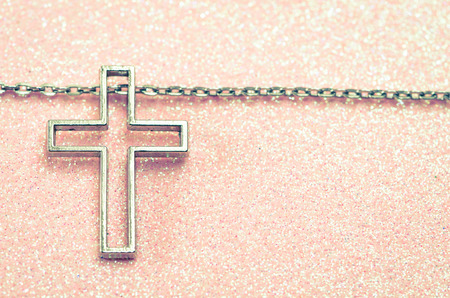 silver cross symbol over pink background photo