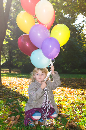 beautiful blond girl holding colorful balloons photo