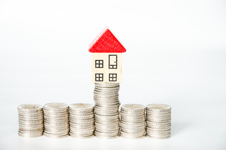 coins in pile and house isolated image Stock Photo
