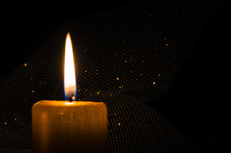 burning candle over dark background