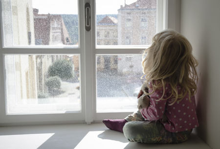 small girl alone looking through window how it is snowing outside 스톡 콘텐츠