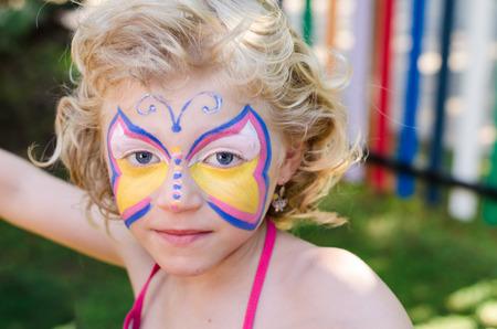 peinture visage: belle jeune fille blonde avec la peinture faciale