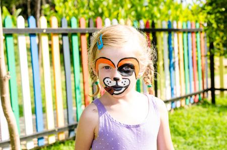 painting face: hermosa chica rubia con cara de pintura del perro