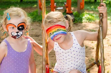painting face: hermosa chica rubia con pintura de la cara del perro y el arco iris
