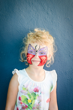 face painting: beautiful blond girl with butterfly face painting Stock Photo