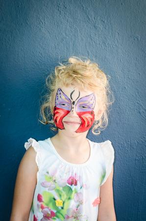 peinture visage: belle jeune fille blonde avec la peinture faciale papillon Banque d'images