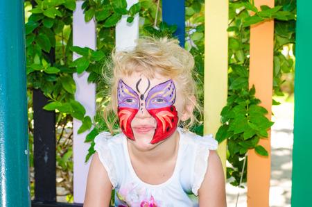 painting face: hermosa chica rubia con pintura de la cara de la mariposa