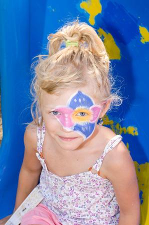 peinture visage: belle jeune fille blonde avec la peinture faciale de fleurs