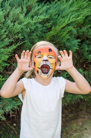peinture visage: belle jeune fille blonde avec la peinture de visage de tigre