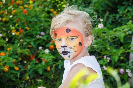 painting face: hermosa chica rubia con pintura de la cara del tigre