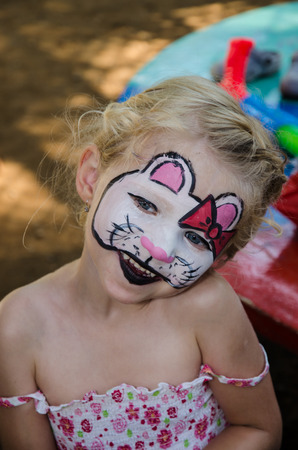 face painting: beautiful blond girl with hallo kitty face painting