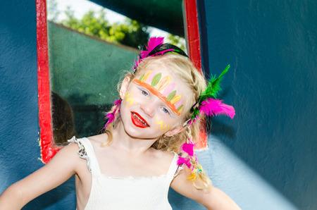 painting face: hermosa chica rubia con pintura de cara indio Foto de archivo