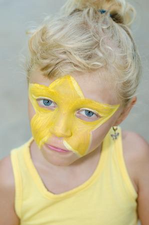 painting face: hermosa chica rubia con pintura de cara estrella amarilla