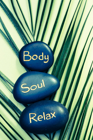 body, soul, relax words written on black lava stones photo