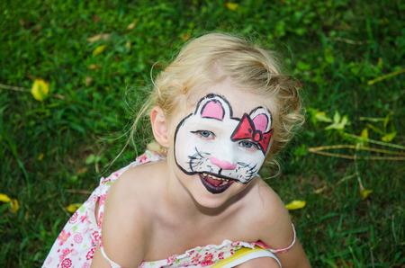 peinture visage: jeune fille blonde avec la peinture de visage de chat