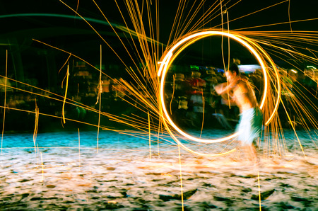 man doing fire show on beach at night photo
