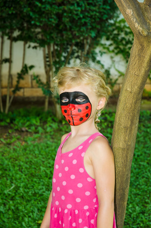 face painting: blond girl with ladybug face painting