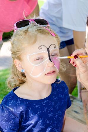 peinture visage: jeune fille blonde avec la peinture faciale