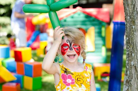 carnaval: jeune fille blonde avec la peinture faciale