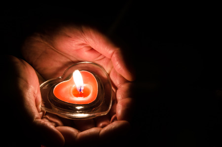 burning candle with heart shape in hands 스톡 콘텐츠