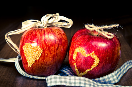 yellow heart: two red apples with yellow heart on them